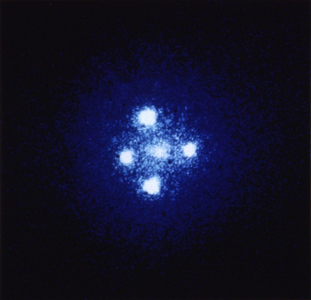 Крест Эйнштейна - прямое доказательство искривления пространства-времени вблизи массивных объектов. На фотографии - изображение одного квазара. Его свет, искривляется пространством вблизи массивной черной дыры (посередине) и доходит до нас в виде четырех отдельных пятен.
