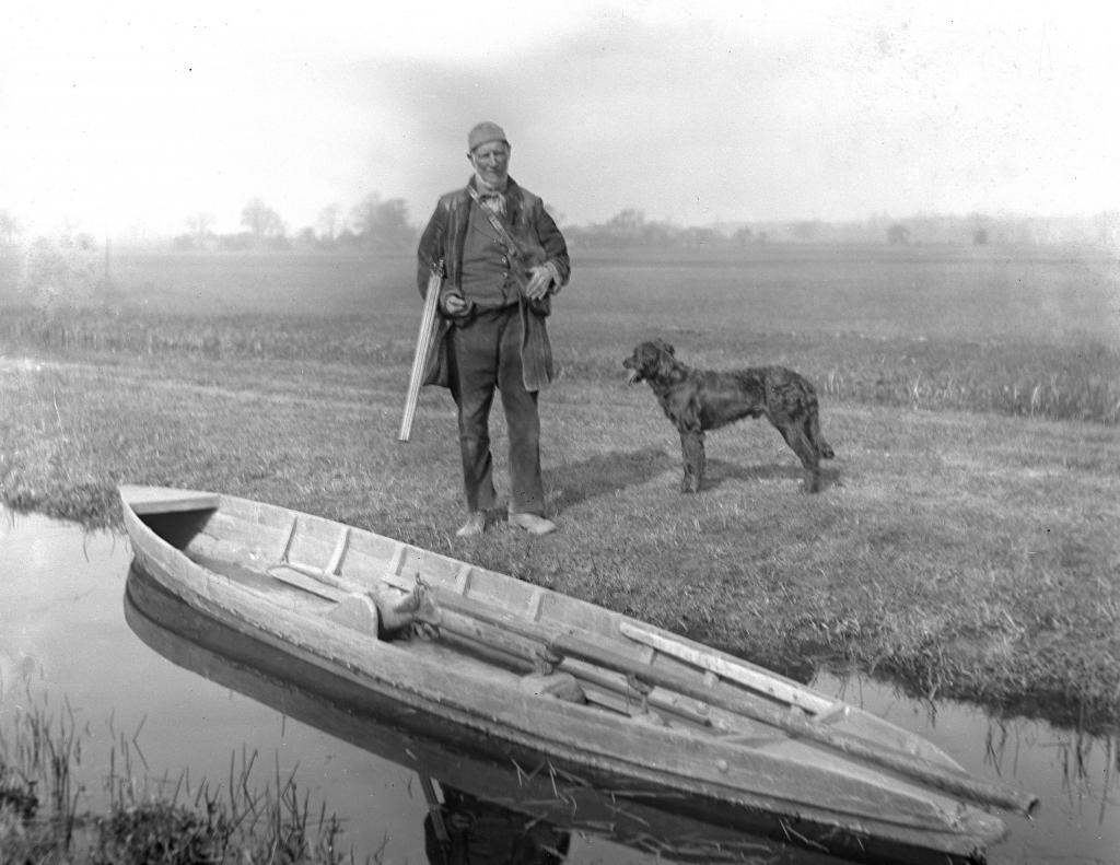 Охотник со своей собакой и лодкой, в которой установлено ружье-уточница